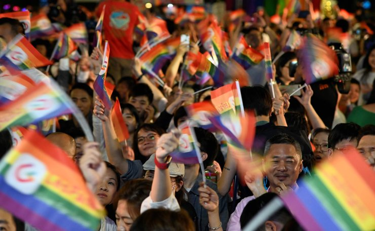 People wave rainbow flags during a mass wedding banquet for gay couples in front of the Presidential Palace in Taipei on May 25, 2019. - Taiwan made history on May 24 with Asia's first legal gay weddings as same-sex couples tied the knot in jubilant and emotional scenes, the culmination of a three-decade fight for equality. AFP