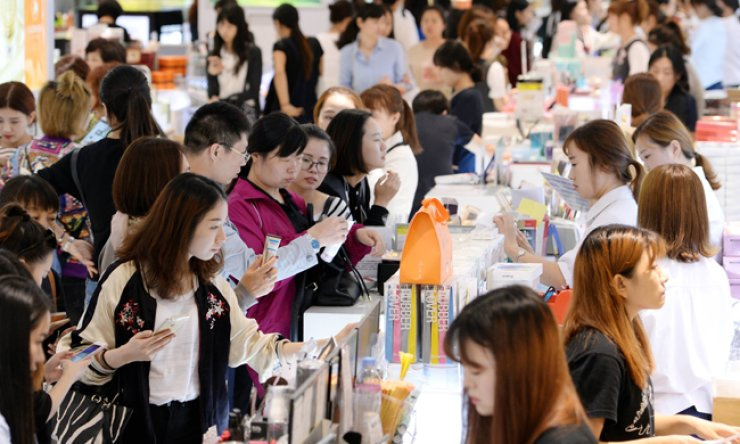 Chinese tourists buy cosmetic products at Lotte Duty Free Shop in Jung-gu, central Seoul. / Korea Times file