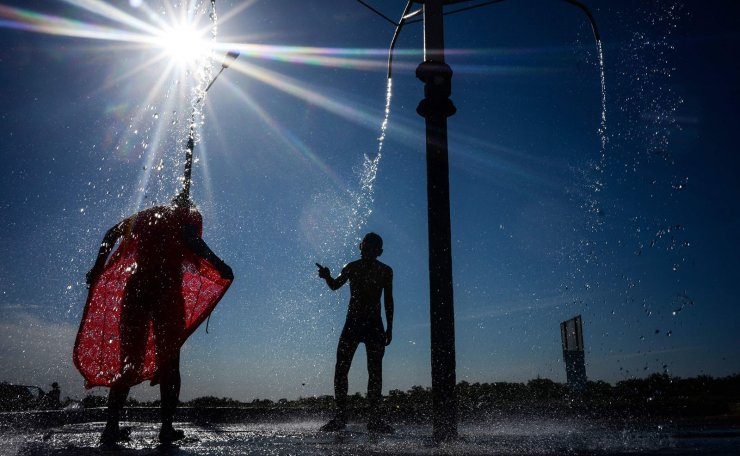 Local residents cool off in a hydrosulfuric spring at the bank of the Syr Darya river in Kazakhstan's city of Baikonur, near the well-known Russian leased cosmodrome, on July 17, 2019. - The temperature in the city reached 39 degrees Celsius. AFP