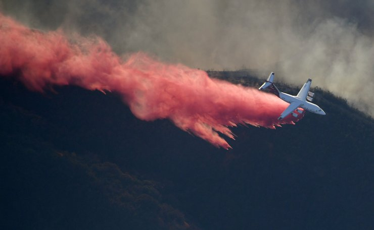 An air tanker drops flame retardant to protect homes as fires burn Friday, Nov. 9, 2018, as seen from a helicopter over the Calabasas section of Los Angeles. AP