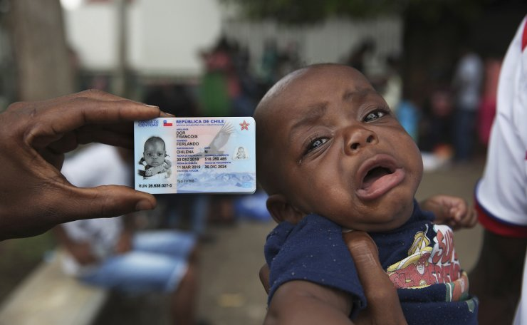 Chilean-born Haitian migrant Fernando Dor Francois, 5-months, cries as he's held next to his Chilean identification card at an immigration detention center where migrants had camped for weeks awaiting word on requests for asylum or permits that would allow them to continue north, in Tapachula, Mexico, Monday, June 3, 2019. President Donald Trump said he will impose a 5% tariff on Mexican goods on June 10 to pressure the Mexican government to block mostly Central American migrants from crossing into the U.S. AP