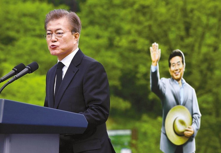 President Moon Jae-in speaks during a memorial service for the late former President Roh Moo-hyun at the latter's hometown of Bongha Village, Gimhae, South Gyeongsang Province, Tuesday, with a cardboard cutout of the late president's figure standing behind him. Moon was Roh's longtime friend and his chief of staff. / Joint press corps