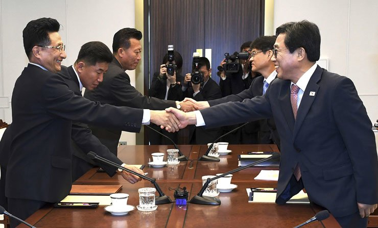 South Korean head delegate Jeon Choong-ryul, right, shakes hands with his North Korean counterpart Won Kil-u ahead of a meeting on inter-Korean sports exchange at the southern side of Panmunjeom, Monday. The Koreas agreed to make a joint entrance and field joint teams at the Asian Games in August, and to hold an inter-Korean basketball competition in July. / Yonhap