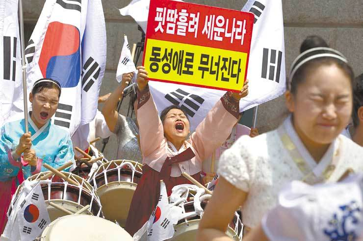 Christian activists stage an anti-gay rally in the streets of central Seoul, June 2016. One of them holds a picket that reads:
