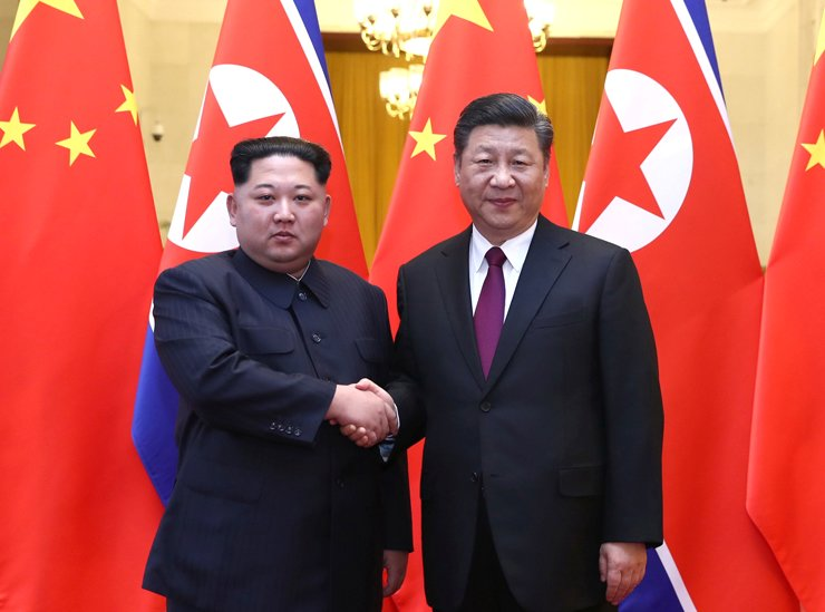 North Korean leader Kim Jong-un and Chinese President Xi Jinping shake hands at the Great Hall of the People in Beijing, Wednesday. / Reuters-Yonhap