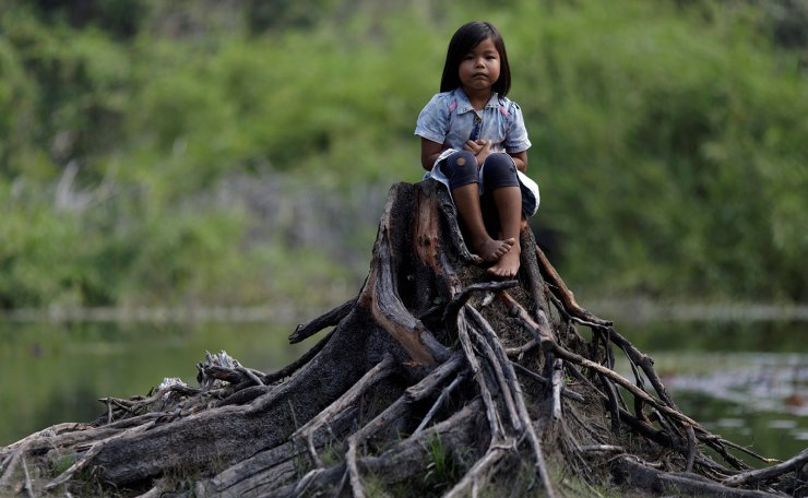 An Indigenous girl from the Parintintin tribe sits on a cut tree trunk in Traira village near Humaita, Amazonas State, Brazil August 16, 2019. Picture taken August 16, 2019. Reuters