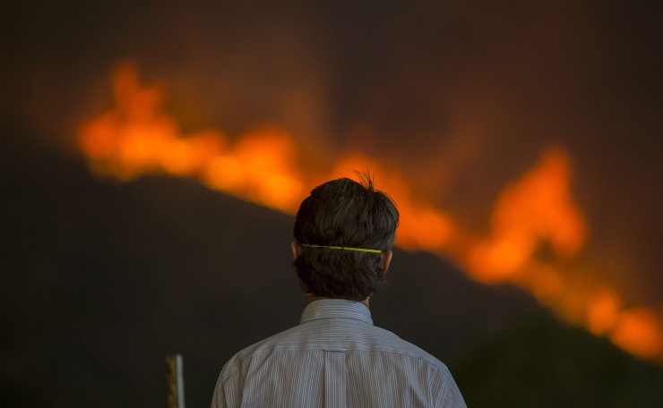 A man watches approaching flames during the Woolsey Fire on November 9, 2018 in Malibu, California. AFP