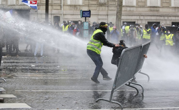 A yellow vests demonstrator rescues another one as police forces use water cannons, Saturday, March 16, 2019 in Paris. French yellow vest protesters clashed Saturday with riot police near the Arc de Triomphe as they kicked off their 18th straight weekend of demonstrations against President Emmanuel Macron. AP