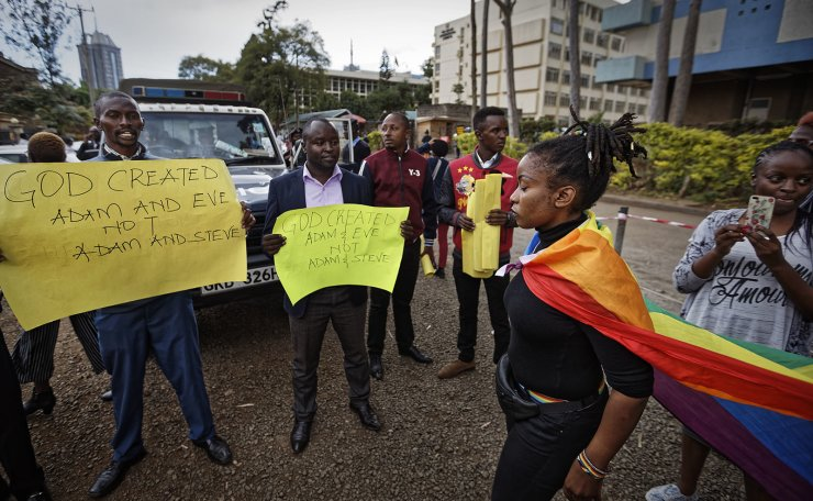 An activist supporting the LGBT community, wearing a rainbow flag, walks past a gathering of Christians opposed to the decriminalization of homosexuality, after a ruling by the High Court in Nairobi, Kenya Friday, May 24, 2019. Kenya's High Court on Friday upheld sections of the penal code that criminalize same-sex relations, a disappointment for gay rights activists across Africa where dozens of countries have similar laws. AP