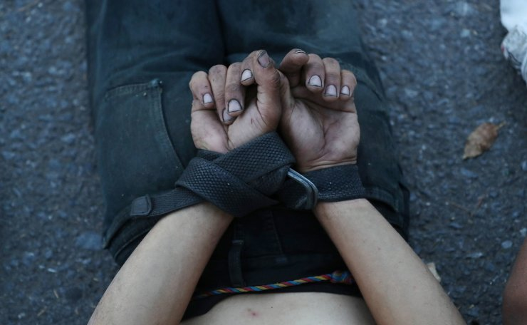 A man lies down on a street as he is detained by security forces after looting during an ongoing blackout in Caracas, Venezuela March 10, 2019. Reuters