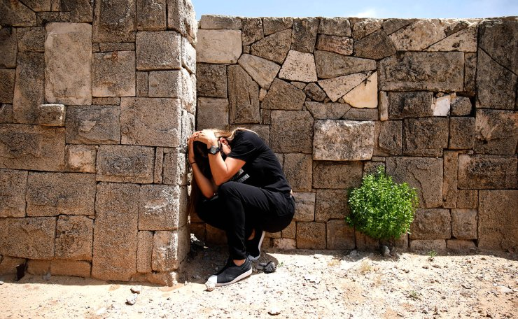 An Israeli takes cover as a siren sounds warning of incoming rockets from Gaza, during cross-border hostilities, in the southern Israeli city of Ashkelon May 5, 2019. Reuters