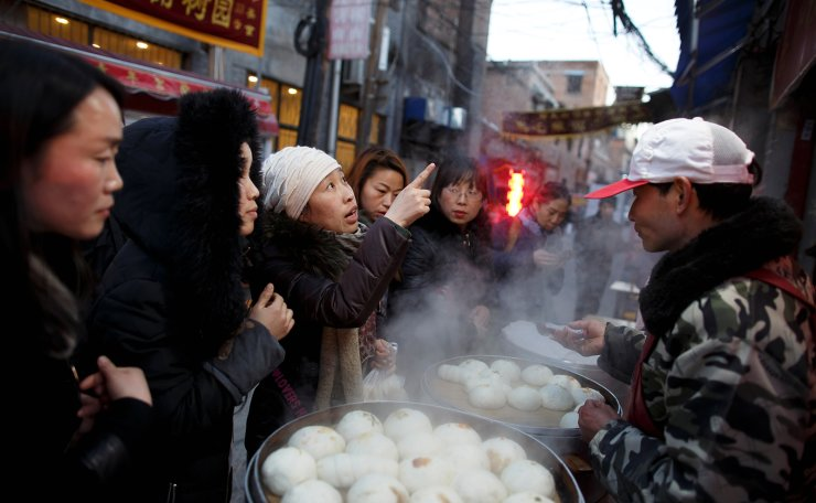 Women buy steamed buns from a street vendor in the old town of Luoyang, Henan province, China January 21, 2019. Reuters