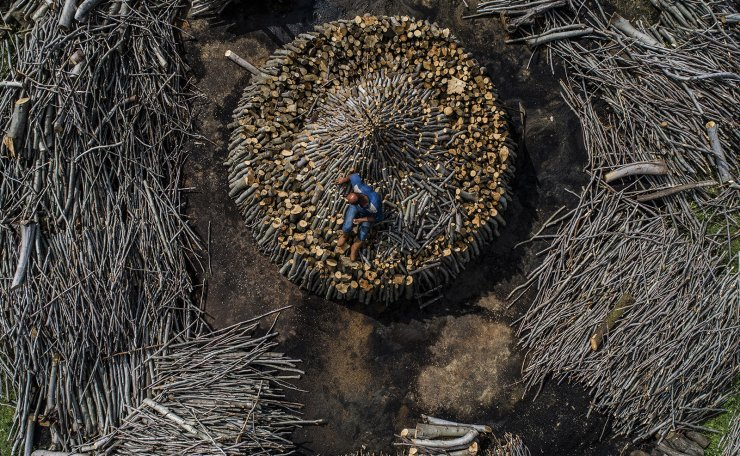 <span>An aerial photo taken by a drone shows, a charcoal worker during preparations for the handcrafted charcoal in Istanbul, Turkey, 24 May 2019 (Issued on 26 May 2019) According to reports, 250,000 tonnes of charcoal are consumed every year in Turkey. Each year in the northern forests of Istanbul, traditional charcoal production starts in the summer The peasants living in the region cut their oak trees and systematically line them up as a circle, Then they covered it with soil and set on fire for a week, it is expected to cool down in two days. EPA</span><br /><br />