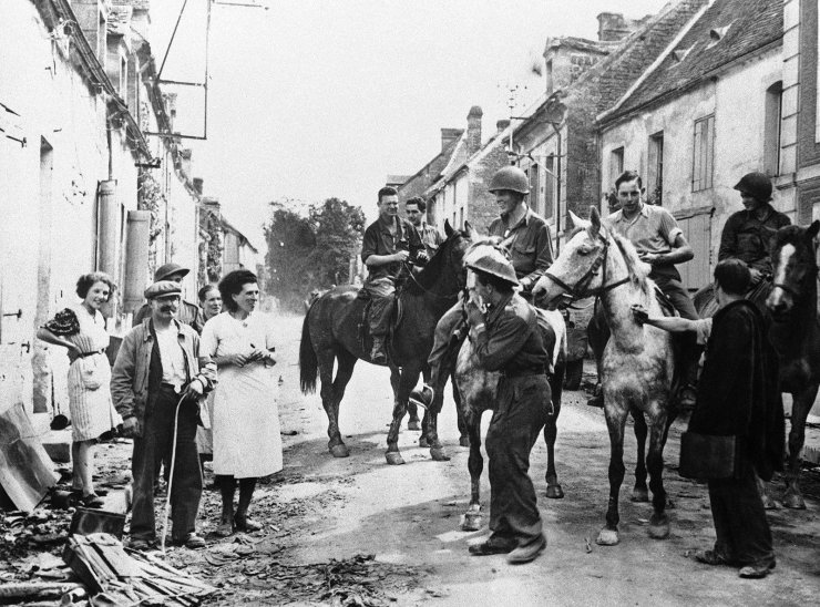 FILE - In this Aug. 30, 1944 file photo, American soldiers ride horses captured from the retreating Germans are met by town residents as they enter the French town of Chambois, Normandy, France. AP