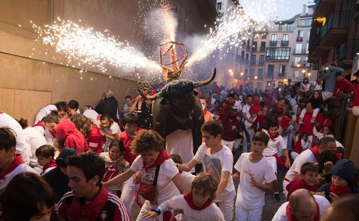 A man wearing a costume of 'Toro de Fuego' (bull of fire) chases people during the San Fermin Festival on July 9, 2019, in Pamplona, northern Spain. AFP