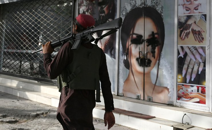In this file photo taken on August 18, 2021, a Taliban fighter walks past a beauty salon with images of women defaced using spray paint in Shar-e-Naw in Kabul. - US President Joe Biden said in an interview that aired August 19, 2021, that war is not the answer to growing fears for the human rights of women in Afghanistan after the Taliban takeover. 'The idea that we're able to deal with the rights of women around the world by military force is not rational,' Biden said in the ABC News interview, his first since the Taliban victory triggered a frantic final US withdrawal. AFP