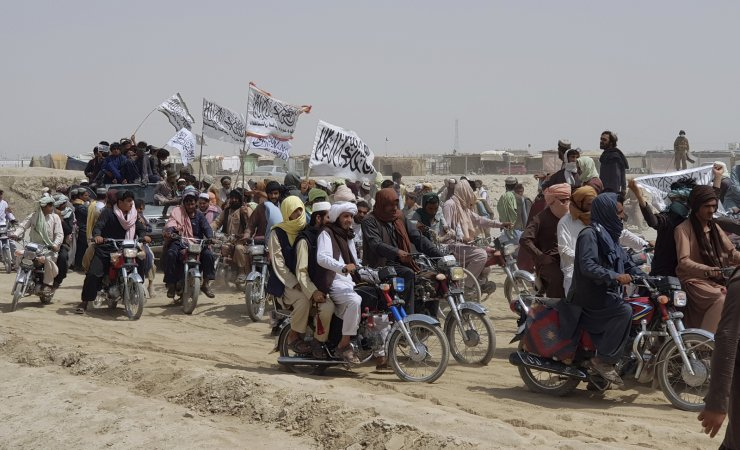 In this July 14, 2021 file photo, supporters of the Taliban carry the Taliban's signature white flags and march in the area of Afghan-Pakistan border, in Chaman, Pakistan. As the Taliban swiftly capture territory in Afghanistan, many Afghans blame Pakistan for the insurgents' success, pointing to their use of Pakistani territory in multiple ways. Pressure is mounting on Islamabad, which initially brought the Taliban to the negotiating table, to get them to stop the onslaught and go back to talks. AP