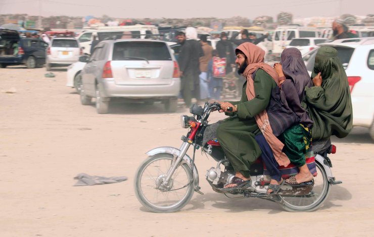 People arrive to go through checking as they prepare to cross into Afghanistan, at Chaman, Pakistan, 15 August 2021. EPA