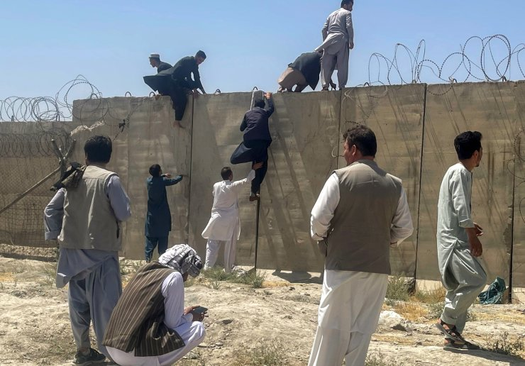 Men try to get inside Hamid Karzai International Airport in Kabul, Afghanistan August 16, 2021. REUTERS