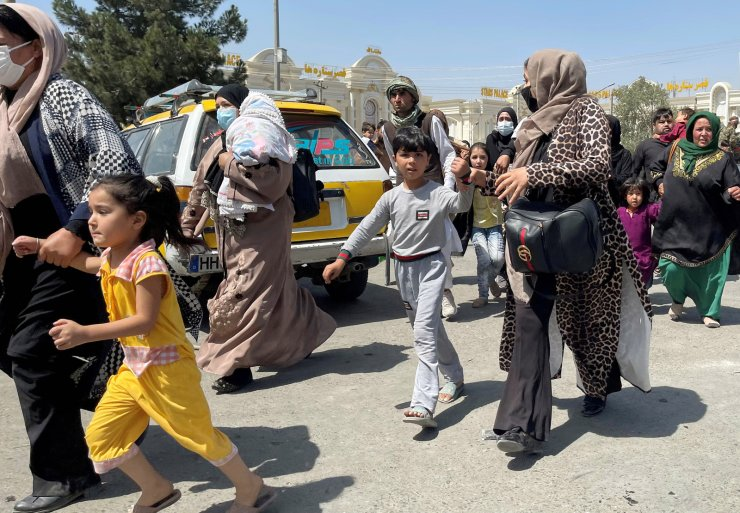 Women with their children try to get inside Hamid Karzai International Airport in Kabul, Afghanistan August 16, 2021. REUTERS