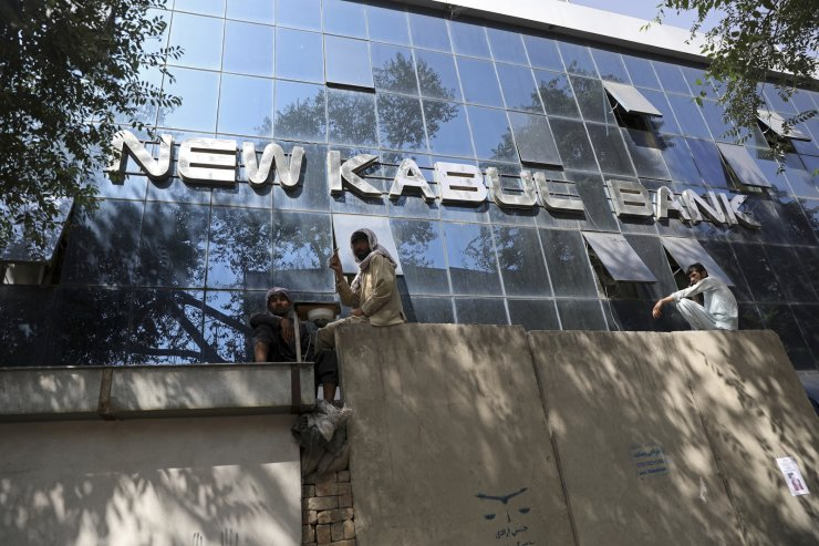 Afghans sit on the wall as people wait for hours to withdraw money, in front of Kabul Bank, in Kabul, Afghanistan, Sunday, Aug. 15, 2021. Officials say Taliban fighters have entered Kabul and are seeking the unconditional surrender of the central government. AP