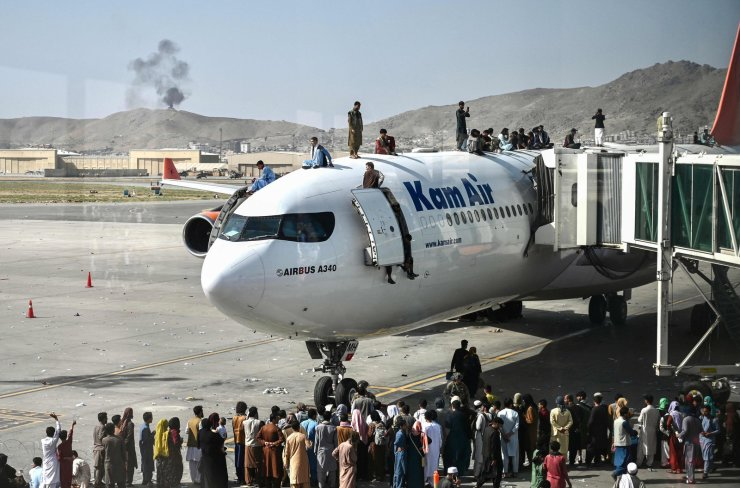 People climb atop a plane as they wait at the Kabul airport in Kabul on August 16, 2021, after a stunningly swift end to Afghanistan's 20-year war, as thousands of people mobbed the city's airport trying to flee the group's feared hardline brand of Islamist rule. AFP