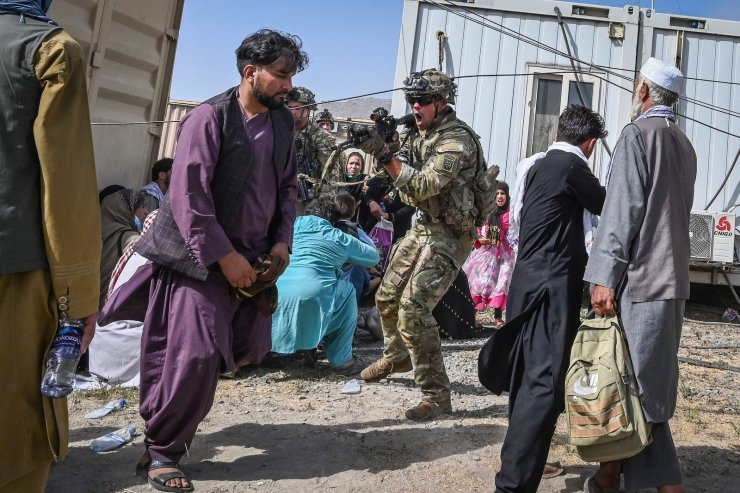 A US soldier (C) point his gun towards an Afghan passenger at the Kabul airport in Kabul on August 16, 2021, after a stunningly swift end to Afghanistan's 20-year war, as thousands of people mobbed the city's airport trying to flee the group's feared hardline brand of Islamist rule. AFP