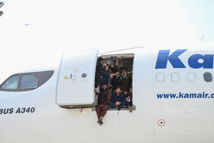 People climb up on a plane and sit by the door as they wait at the Kabul airport in Kabul on August 16, 2021. AFP