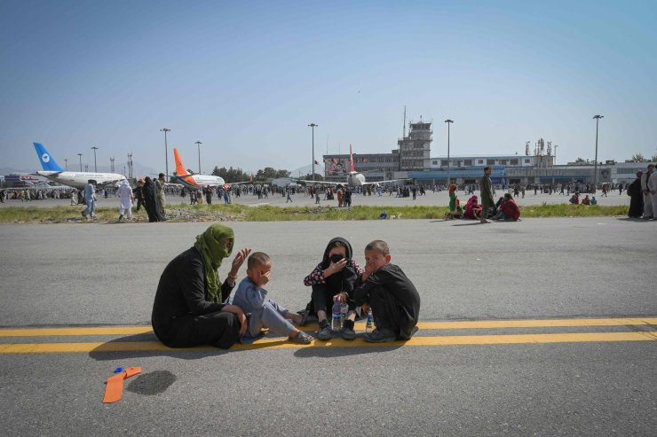 People sit along the tarmac as they wait to leave the Kabul airport in Kabul on August 16, 2021. AFP