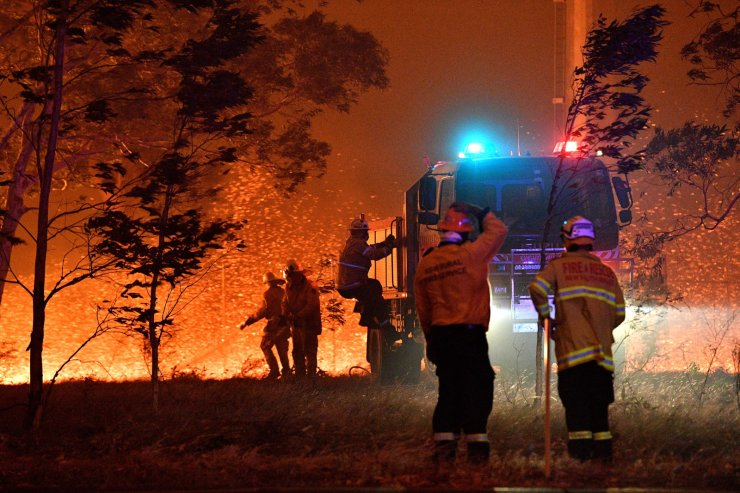 Firefighters hose down trees as they battle against bushfires around the town of Nowra in the Australian state of New South Wales on Dec. 31, 2019. Thousands of holidaymakers and locals were forced to flee to beaches in fire-ravaged southeast Australia on December 31, as blazes ripped through popular tourist areas leaving no escape by land. AFP