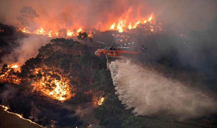 A handout photo taken and received on December 31, 2019 from the State Government of Victoria shows a helicopter fighting a bushfire near Bairnsdale in Victoria's East Gippsland region. AFP