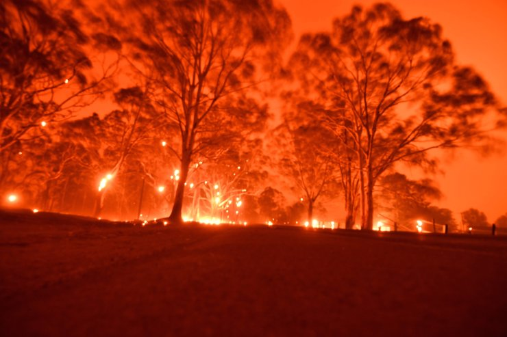 The afternoon sky glows orange from bushfires in the area around the town of Nowra in the Australian state of New South Wales on Dec. 31, 2019. AFP