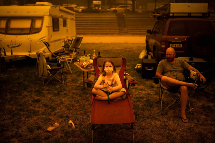 Amy (L) and Ben Spencer sit at the showgrounds in the southern New South Wales town of Bega where they are camping after being evacuated from nearby sites affected by bushfires on Dec. 31, 2019. AFP