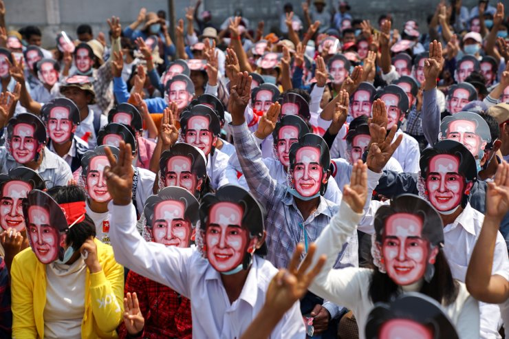 Protesters wearing masks depicting ousted leader Aung San Suu Kyi, flash three-finger salutes as they take part in a protest against the military coup in Yangon, Myanmar, February 28, 2021. REUTERS
