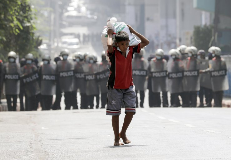 A boy carries a sack of rice past anti-riot police officers blocking a road during a protest against the military coup, in Yangon, Myanmar, 26 February 2021 Anti-coup protests continue in Myanmar amid regional diplomatic attempts to reach a resolution to weeks of unrest caused by the military coup. EPA