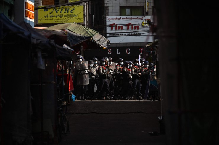 Police march on a road to clear away protesters from holding a demonstration against the military coup in Yangon on February 26, 2021. AFP