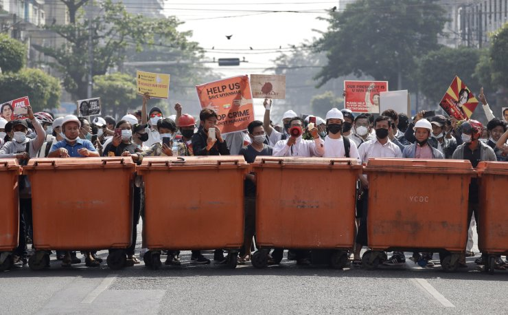 Demonstrators stand behind a barrier of waste containers as they face riot police during a protest against the military coup, in Yangon, Myanmar, 28 February 2021. Security forces intensified their use of force to crack down on anti-coup demonstrations following weeks of unrest since the 01 February military coup. EPA