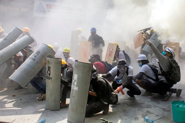 Protesters take cover as they clash with riot police officers during a protest against the military coup in Yangon, Myanmar, February 28, 2021. REUTERS