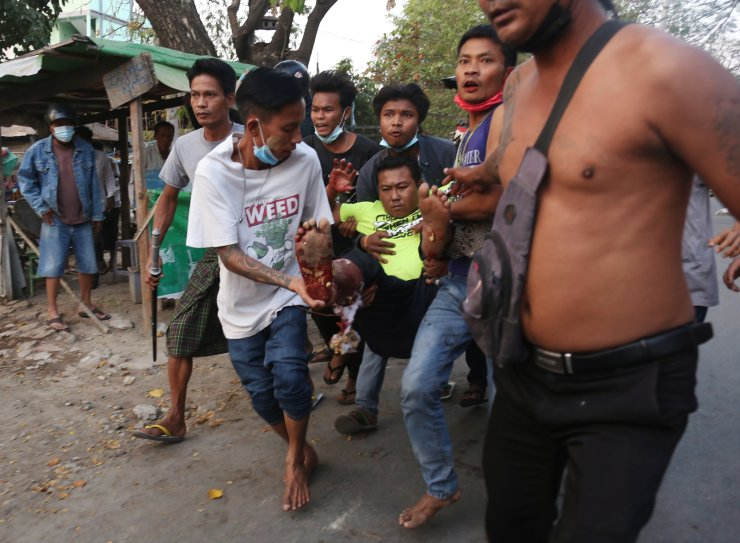 People carry an injured man after police cracked down on demonstrators during a protest against the military coup in Mandalay, Myanmar, 28 February 2021. Several people were killed on 28 February and many injured as security forces intensified their use of force to crack down on anti-coup demonstrations following weeks of unrest since the 01 February military coup. EPA