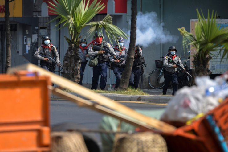 A riot police officer fires a teargas canister to disperse protesters taking part in a rally against the military coup in Yangon, Myanmar, February 27, 2021. REUTERS