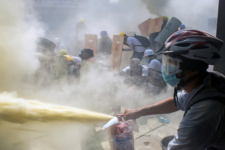 A protester sprays a fire extinguisher as demonstrators clash with riot police officers during a protest against the military coup in Yangon, Myanmar, February 28, 2021. REUTERS