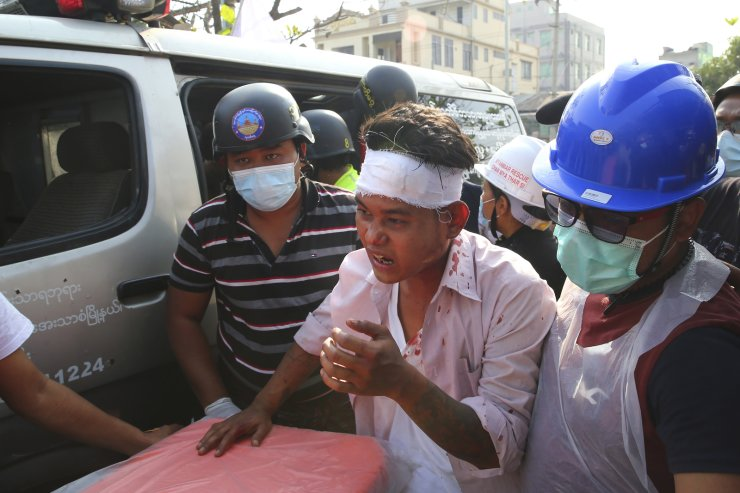 An injured protester is escorted as police tried to disperse a demonstration against the military coup in Mandalay, Myanmar, Friday, Feb. 26, 2021. Security forces in Myanmar's largest city on Friday fired warning shots and beat truncheons against their shields while moving to disperse more than 1,000 anti-coup protesters. AP