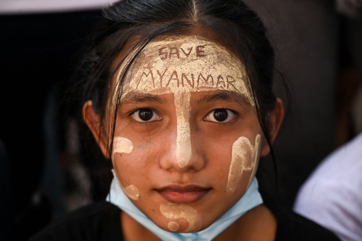A protester wearing traditional 'thanakha', a yellowish-white cosmetic paste made from ground bark applied on the face, poses for a picture during a demonstration against the military coup in Yangon on February 25, 2021. AFP