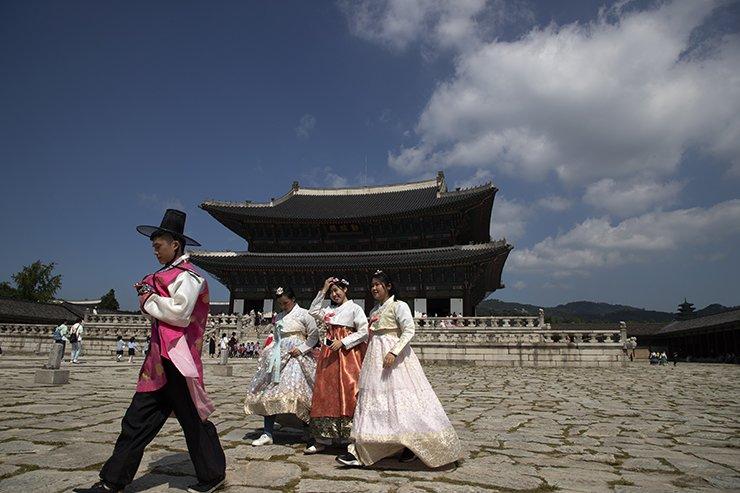 Foreign tourists wearing hanbok walk the courtyard at Gyeongbok Palace in Seoul, Monday. /Korea Times photo by Choi Won-suk