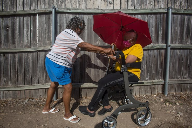 From left, Faye LeCesne assists Adrian Johnson as they move forward while waiting in line to vote early in the general election outside the Comal County Election Office in New Braunfels, Texas on Tuesday, Oct. 13, 2020. 'I don't mind standing in the heat — we worked so hard to have this right,' Johnson said. 'As long as I can breathe, I'm voting.'  AP
