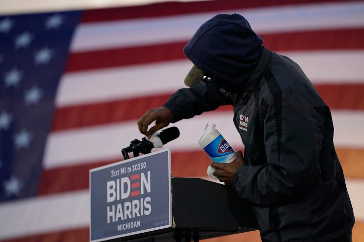 The podium is wiped down prior to Democratic presidential candidate former Vice President Joe Biden speaking at Michigan State Fairgrounds in Novi, Mich., Friday, Oct. 16, 2020. AP