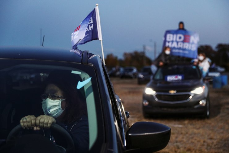 People sit in and on top of their vehicles at a voter mobilization event where U.S. Democratic presidential candidate Joe Biden delivers remarks at the Michigan State Fairgrounds in Novi, Michigan, October 16, 2020. Reuters