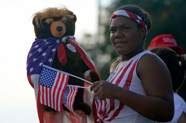 Mia James, 14, holds up her Donald Trump bear as she waves flags along with other supporters of President Donald Trump as they wait for Democratic presidential candidate former Vice President Joe Biden's motorcade to arrive, Tuesday, Oct. 13, 2020, at Miramar Regional Park in Miramar, Fla. AP