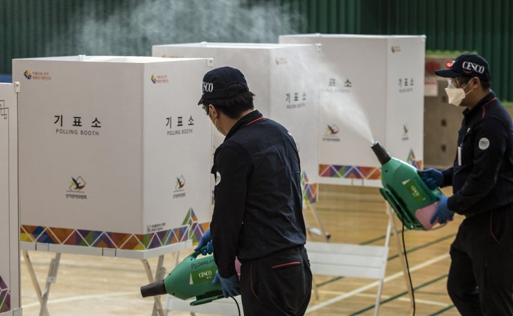 A worker wearing a face mask and goggles sprays disinfectant to help stop the spread of the spread of the new coronavirus ahead of the voting for the general elections at a local polling station in Seoul, South Korea, Tuesday, April 14, 2020. Korea Times photo by Choi Won-suk