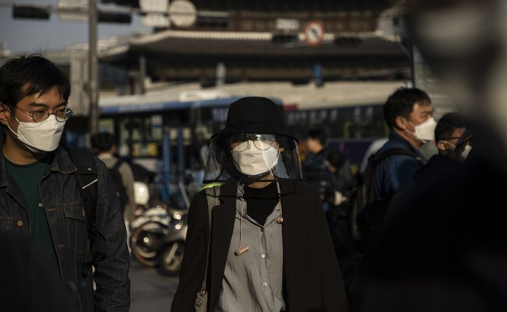 People wearing face masks to help protect against the spread of the new coronavirus are seen on the street in Seoul, April 14, 2020. Korea Times photo by Choi Won-suk